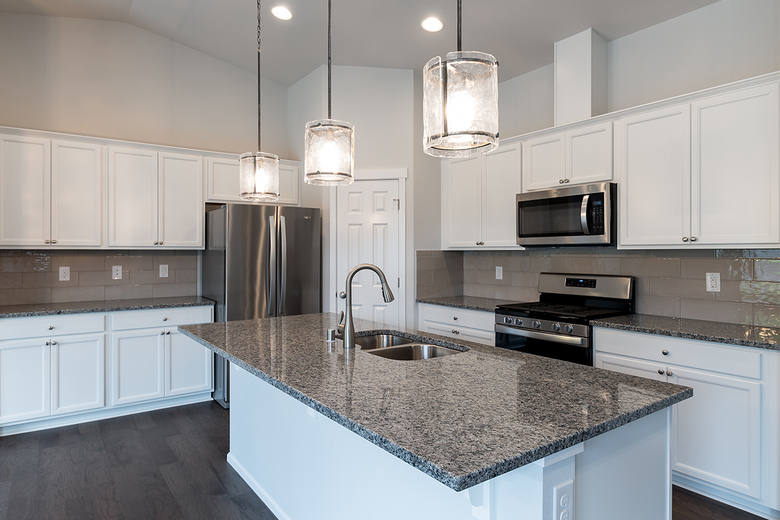 Kitchens feature solid-surface countertops, white painted millwork and engineered wood flooring.
