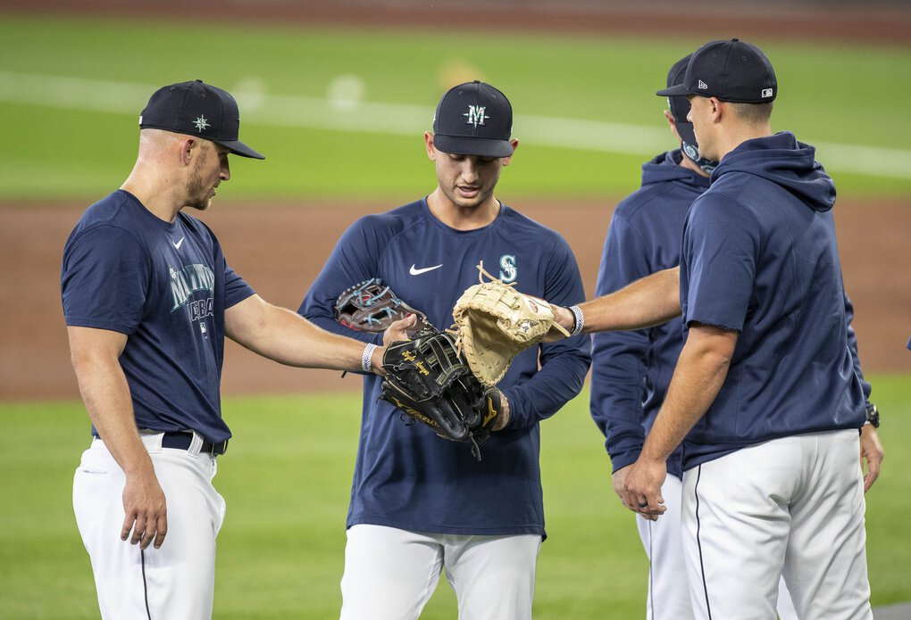 Mariners infielders Kyle Seager, left, Tim Lopes and Evan White conclude their fielding drills. (Dean Rutz / The Seattle Times)