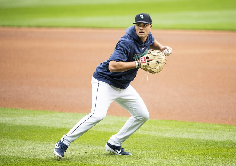 Evan White fields grounders at first Saturday. (Dean Rutz / The Seattle Times)