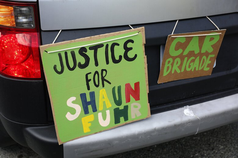 One of the lead cars has protest signs during the 'Justice for Shaun Fuhr' march in the South Lake Union neighborhood of Seattle, Monday, July 6, 2020. (Ken Lambert / The Seattle Times)