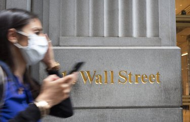 A woman wearing a mask passes a sign for Wall Street, Tuesday, June 30, 2020, during the coronavirus pandemic. (AP Photo/Mark Lennihan) NYML102 NYML102