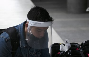 A traveler wearing a face shield looks at his phone outside the arrivals area at Los Angeles International Airport on Wednesday, June 24, 2020, in Los Angeles. The United States recorded a one-day total of 34,700 new COVID-19 cases, the highest in two months, according to the count kept by Johns Hopkins University. (AP Photo/Jae C. Hong) CAJH103 CAJH103