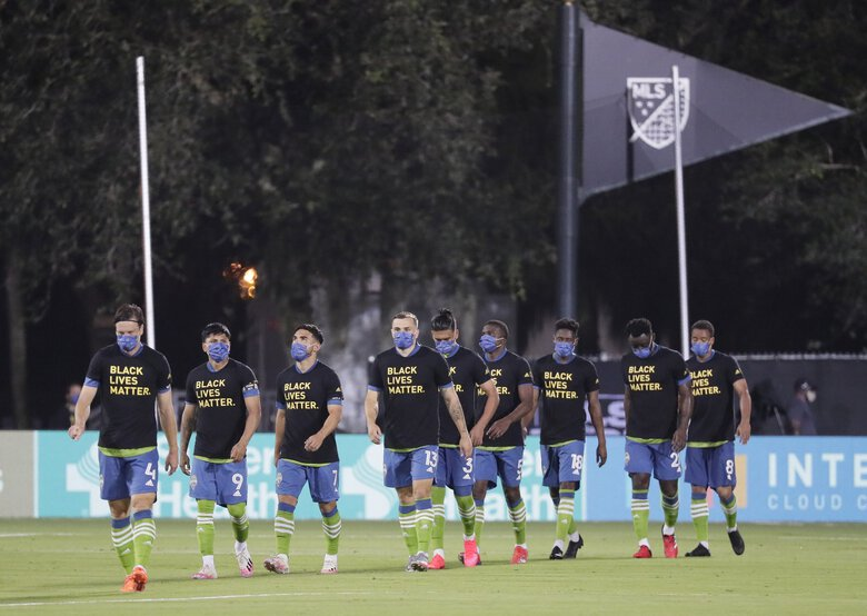 Seattle Sounders players, wearing masks take the field before the start of an MLS soccer match against the San Jose Earthquakes Friday in Kissimmee, Fla. (John Raoux / The Associated Press)