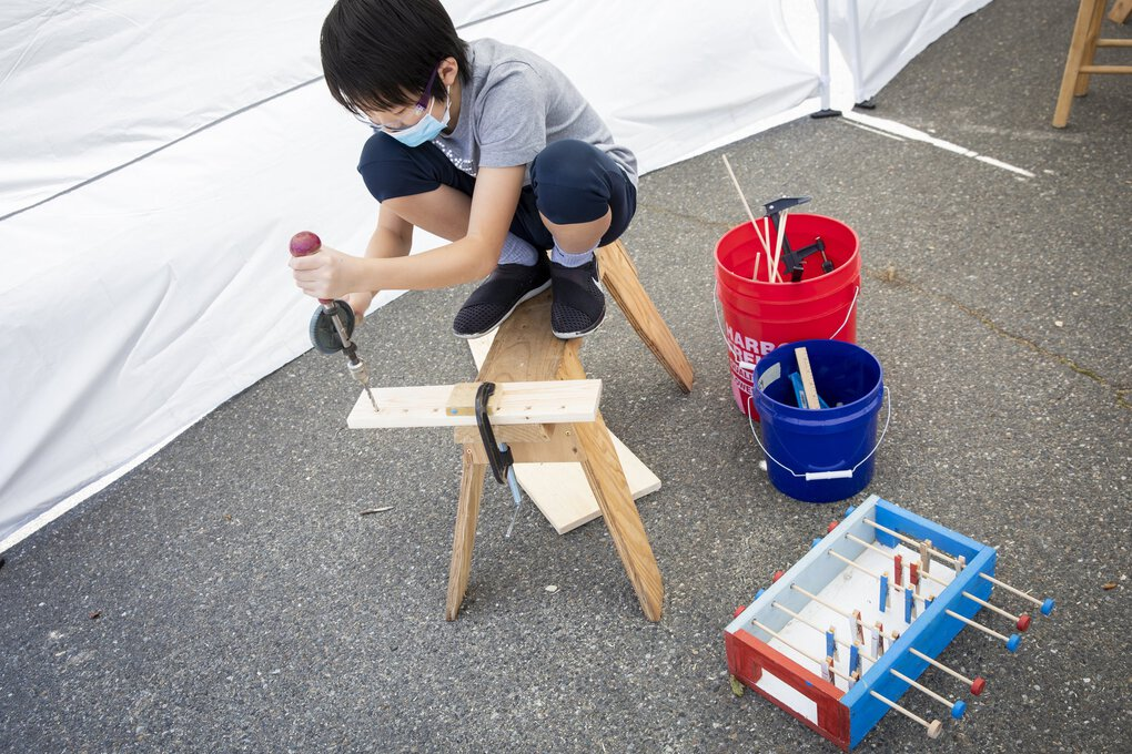 Henry Zhu, 12, uses a manual hand drill to make holes for a foosball table during a half-day summer camp class with Kids' Carpentry Seattle in the Columbia City neighborhood Friday. (Bettina Hansen / The Seattle Times)