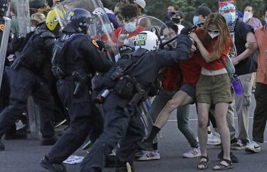 Protesters clash with police officers near the district attorney's office Thursday, July 9, 2020, in Salt Lake City. Two police officers in Utah were cleared earlier Thursday in the death of Bernardo Palacios-Carbajal, an armed man shot at more than 30 times as he ran from police, a decision that prompted his grieving family to heighten their calls for systematic changes to law enforcement. (AP Photo/Rick Bowmer) UTRB121 UTRB121