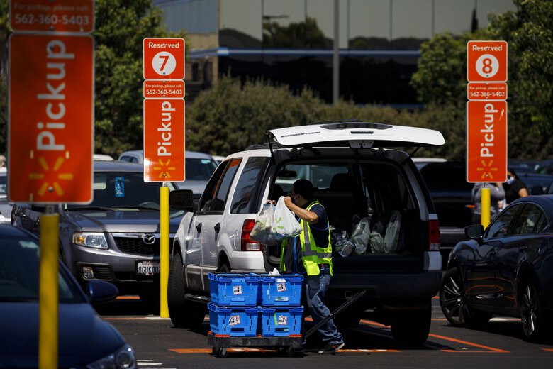An employee wearing a protective mask loads online pick-up order items into a customer's vehicle outside a Walmart store in Lakewood, Calif., on July 16. (Patrick T. Fallon / Bloomberg)