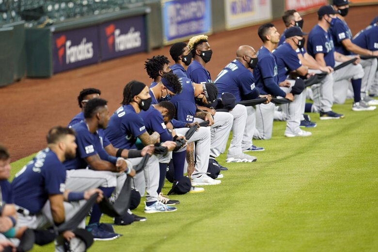 Seattle Mariners players kneel for social justice before the game. (David J. Phillip / Associated Press)