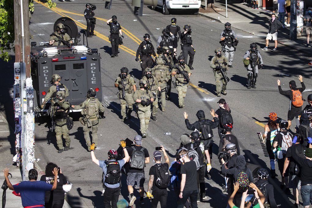 "Seattle police and SWAT team members, using an armored vehicle marked ""Bellevue Police,"" retreat east on Pine Street toward the East Precinct after a back-and-forth with protesters near Seattle Central College. (The Seattle Times)"