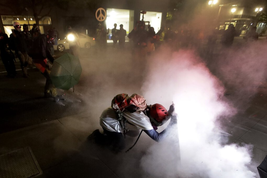 A demonstrator kneels and uses a makeshift shield as federal agents launch tear gas during a protest at the federal courthouse in Portland on Wednesdy.  (Marcio Jose Sanchez / The Associated Press)