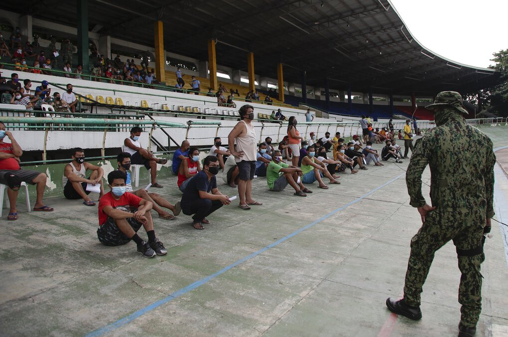 Police watch as people who were apprehended for violating quarantine health protocols wait to be released at the Amoranto Sports Complex in Manila, Philippines, on Wednesday. (Aaron Favila / The Associated Press)