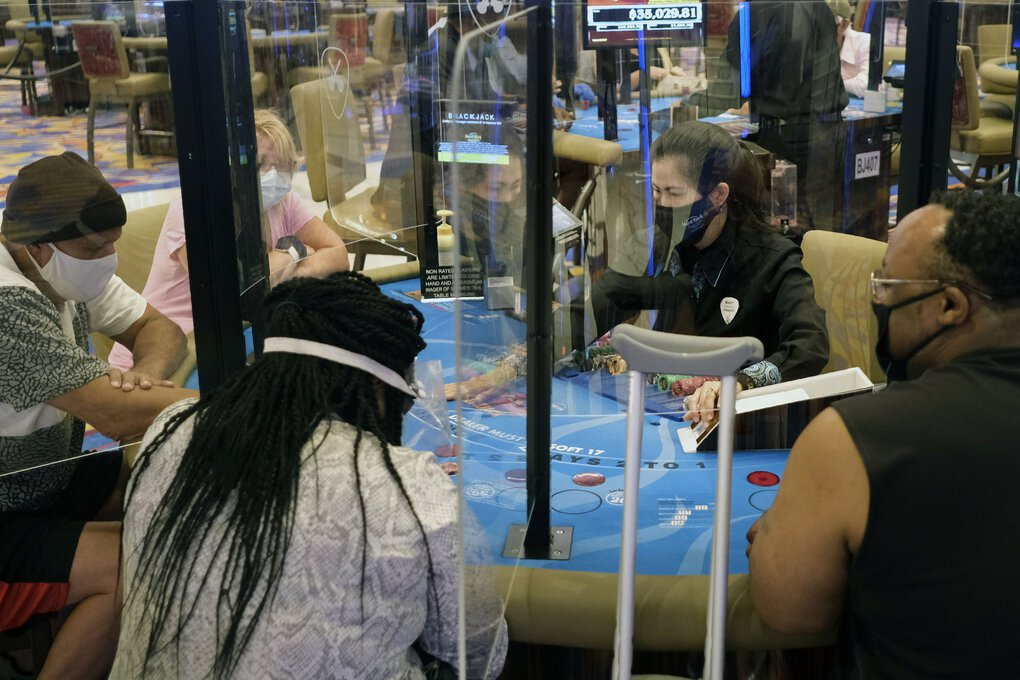 Partitions between players and face masks allow gamblers to play card games at the Hard Rock Casino in Atlantic City, N.J., on Thursday. Eager to hit the slot machines and table games after a 108-day absence, gamblers wore face masks and did without smoking and drinking as Atlantic City's casinos reopened Thursday amid the coronavirus pandemic. (Seth Wenig / The Associated Press)