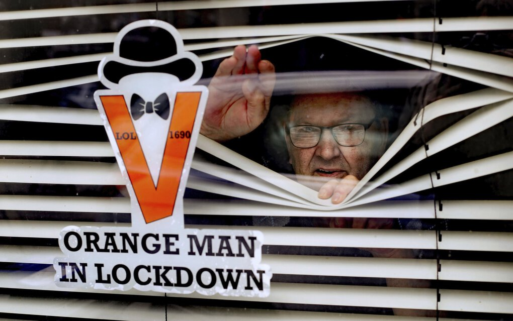In Belfast, Randy Davidson, who is isolating at home, poses with a sticker in his window to celebrate the 12th of July holiday on Monday, July 13, 2020, as traditional large-scale parades were canceled this year due to the pandemic. The Twelfth marks the anniversary of the victory of Protestant William of Orange over Catholic King James II at the Battle of the Boyne in July 1690. The holiday was observed on Monday this year because the 12th fell on a Sunday. (Niall Carson / The Associated Press)