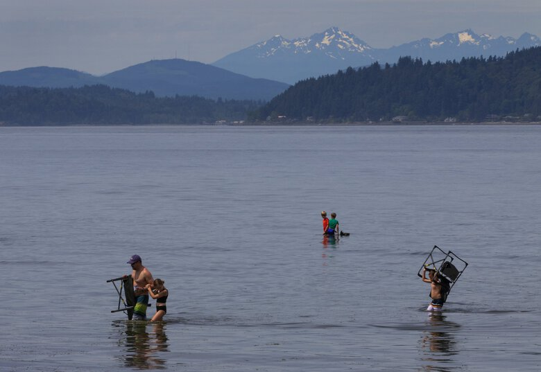 When the tide started to come in at Alki Beach in Seattle Friday, June 19, 2020, a family picked up chairs and left the sandbar where they had been sitting and headed towards the shore. (Ellen M. Banner / The Seattle Times)