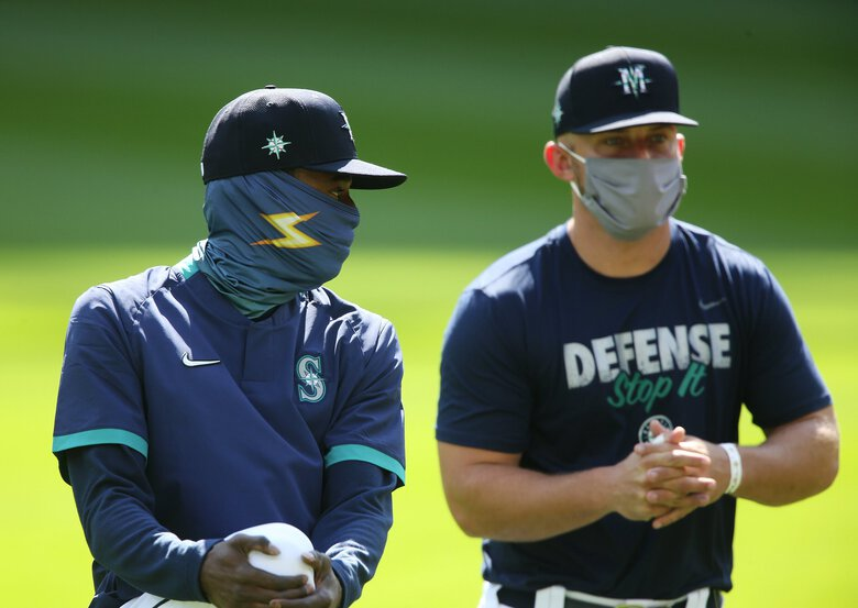 """Second baseman Dee Gordon, left, and third baseman Kyle Seager, right, are seen stretching during the third day of Mariners """"Summer Camp"""" training, Sunday, July 5, 2020 at T-Mobile Park in Seattle.(Ken Lambert / The Seattle Times)"""