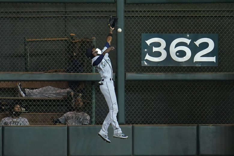 Seattle Mariners left fielder Dee Gordon leaps as he attempts to catch an RBI-triple by Houston Astros' Dustin Garneau during the fourth inning of a baseball game Monday, July 27, 2020, in Houston. (David J. Phillip / The Associated Press)