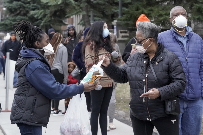 FILE – In this April 7, 2020, file photo, a worker hands out disinfectant wipes and pens as voters line up outside Riverside High School for Wisconsin's primary election in Milwaukee. Many Black voters are skeptical of voting by mail even as states seek to expand that option during the coronavirus pandemic. Decades of racism and voter disenfranchisement are at the heart of the uneasy choice facing Black voters. (AP Photo/Morry Gash, File)