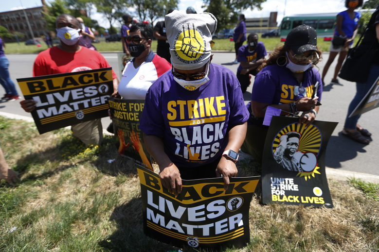 """Charlene Smith kneels with protesters during a rally outside Hartford Nursing & Rehabilitation Center in Detroit, Monday, July 20, 2020. The national workers strike, dubbed the """"Strike for Black Lives,"""" saw people walk off the job Monday in U.S. cities to protest systemic racism and economic inequality. (AP Photo/Paul Sancya)"""