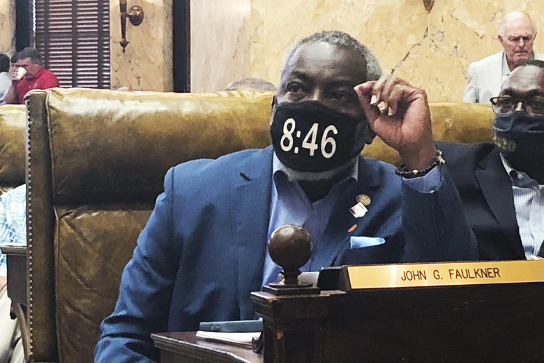 FILE – In this Saturday, June 27, 2020, file photo, Mississippi state Rep. John Faulkner, D-Holly Springs, wears a mask in honor of George Floyd, in the House chamber of the Mississippi Capitol in Jackson, Miss. Faulkner posted a video to Facebook late Wednesday, July 8, saying he tested positive for the virus and has had mild symptoms akin to a sinus infection with an occasional cough. (AP Photo /Emily Wagster Pettus, File)