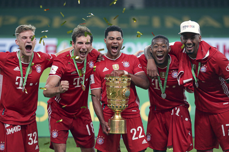 Bayern Munich players celebrate with the trophy after winning the German soccer cup (DFB Pokal) final match between Bayer 04 Leverkusen and FC Bayern Munich in Berlin, Germany, Saturday, July 4, 2020. (AP Photo/Michael Sohn)
