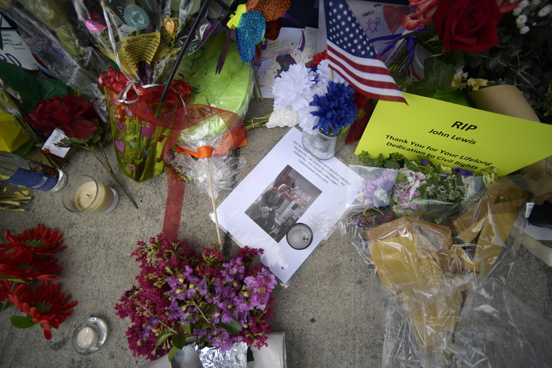 """Flowers and other mementos are seen at a make-shift memorial near the home of Rep. John Lewis, D-Ga., Sunday, July 19, 2020, in Atlanta. Lewis, who died Friday at age 80, was the youngest and last survivor of the Big Six civil rights activists who organized the 1963 March on Washington, and spoke shortly before the group's leader, Rev. Martin Luther King Jr., gave his """"I Have a Dream"""" speech to a vast sea of people. (AP Photo/Mike Stewart)"""