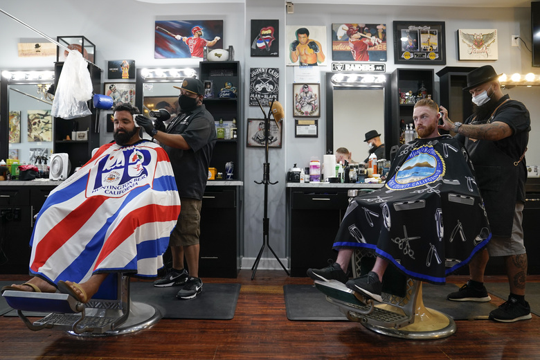 Ricardo Rivera, left, has his hair cut by Anthony Acosta while Braunson McDonald has his hair cut by Luis Lopez, right, owner of Orange County Barbers Parlor, Wednesday, July 15, 2020, in Huntington Beach, Calif. California Gov. Gavin Newsom this week ordered that indoor businesses like salons, barber shops, restaurants, movie theaters, museums and others close due to the spread of COVID-19. (AP Photo/Ashley Landis)