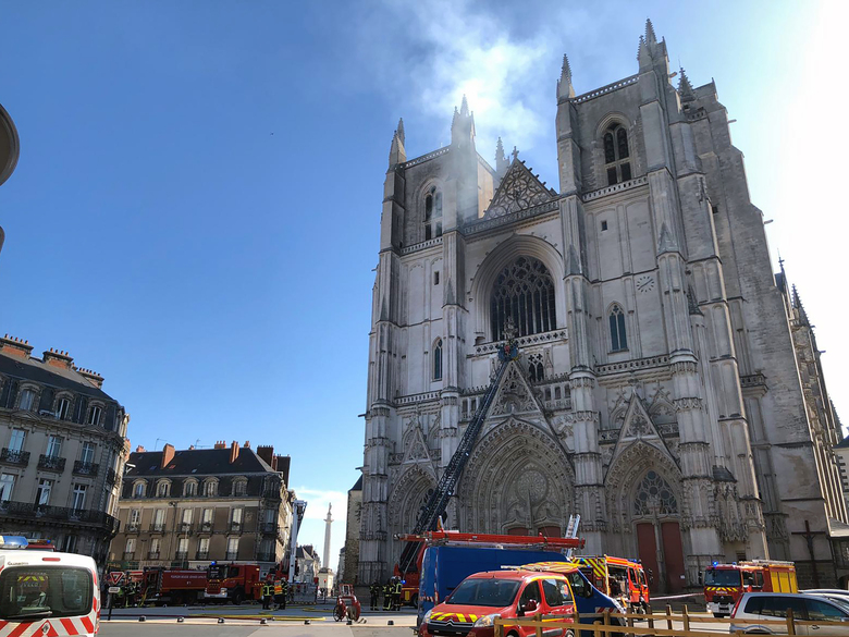 Fire fighters brigade work to extinguish the blaze at the Gothic St. Peter and St. Paul Cathedral, in Nantes, western France, Saturday, July 18, 2020. The fire broke, shattering stained glass windows and sending black smoke spewing from between its two towers of the 15th century, which also suffered a serious fire in 1972. The fire is bringing back memories of the devastating blaze in Notre Dame Cathedral in Paris last year that destroyed its roof and collapsed its spire and threatened to topple the medieval monument. (AP Photo/Laetitia Notarianni)