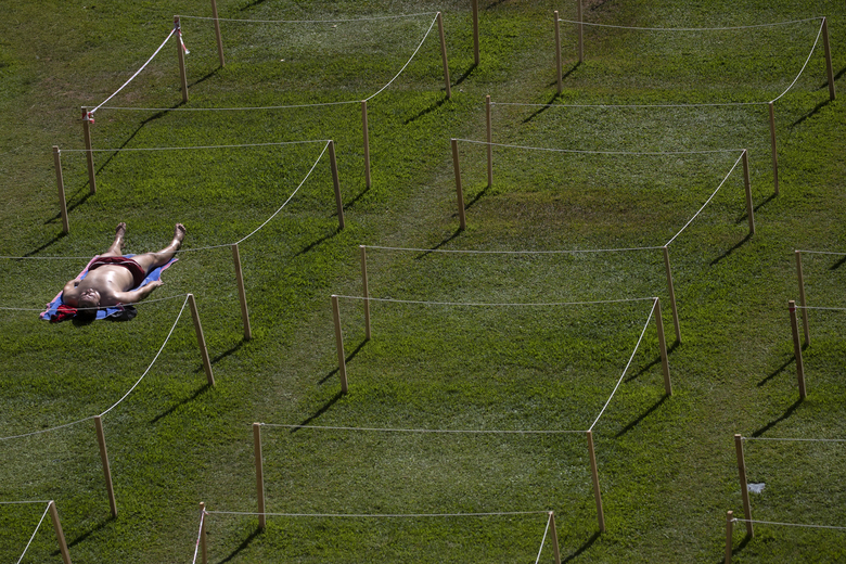 A man sunbathes on a hot day of summer in Rivas Vaciamadrid, Spain, Friday, July 31, 2020. Spain's national weather agency says several parts of the country have set record temperatures during a heatwave. (AP Photo/Manu Fernandez)