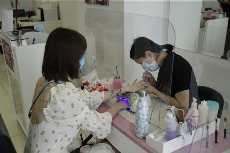 A customer receives a Gelish manicure at Lily's Nails & Beauty on Clerkenwell Road in London, Monday, July 13, 2020. Nail bars, beauty salons, tattoo and massage studios, are among businesses able to reopen in the latest lifting of restrictions in England put in place to stem the spread of coronavirus. (AP Photo/Matt Dunham)