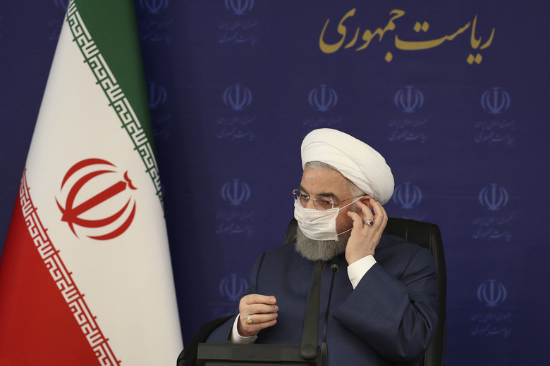 "In this photo released by the official website of the office of the Iranian Presidency, President Hassan Rouhani adjusts his face mask in a meeting of the national headquarters of the fight against the COVID-19, in Tehran, Iran, Saturday, July 18, 2020. He estimated as many as 25 million Iranians could have been infected with the coronavirus since the outbreak's beginning, citing an Iranian Health Ministry study that has so far not been made public, the state-run IRNA news agency reported. Writing in Farsi at top right reads, ""The Presidency."" (Iranian Presidency Office via AP)"