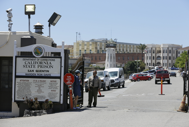 "In this file photo, a Department of Corrections officer guards the main entryway leading into San Quentin State Prison in San Quentin, Calif., July 24, 2019. California lawmakers harshly criticized state corrections officials Wednesday, July 1, 2020, for a ""failure of leadership"" for botching their handling of the pandemic by inadvertently transferring infected inmates to an untouched prison, triggering the state's worst prison coronavirus outbreak. A third of the 3,500 inmates at San Quentin State Prison near San Francisco have tested positive since officials transferred 121 inmates from the heavily impacted California Institution for Men in Chino on May 30 without properly testing them for infections. (AP Photo/Eric Risberg, File)"