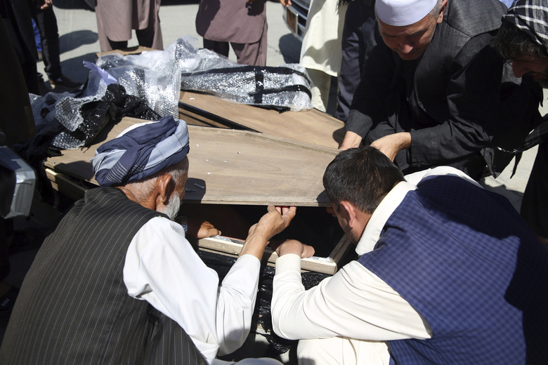 Families identify bodies of their relatives who drowned after their boat sank in Turkey's Lake Van, at the Hamid Karzai International Airport in Kabul, Afghanistan, Wednesday, July 22, 2020. The boat sank last month while ferrying dozens of migrants across a lake in eastern Turkey. (AP Photo/Rahmat Gul)