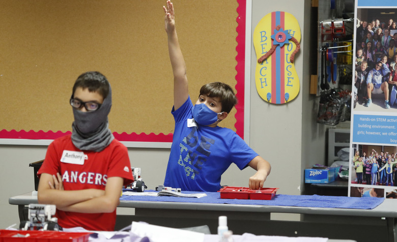 Amid concerns of the spread of COVID-19, Aiden Trabucco, right, wears a mask as he raises his hand to answer a question behind Anthony Gonzales during a summer STEM camp at Wylie High School Tuesday, July 14, 2020, in Wylie, Texas. (AP Photo/LM Otero)