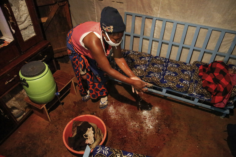 Traditional birth attendant Emily Owino cleans up after helping Veronica Atieno deliver her daughter Shaniz Joy Juma in Emily's one-room house during a dusk-to-dawn curfew, in the Kibera slum of Nairobi, Kenya in the early hours of Friday, May 29, 2020. Kenya already had one of the worst maternal mortality rates in the world, and though data are not yet available on the effects of the curfew aimed at curbing the spread of the coronavirus, experts believe the number of women and babies who die in childbirth has increased significantly since it was imposed mid-March. (AP Photo/Brian Inganga)