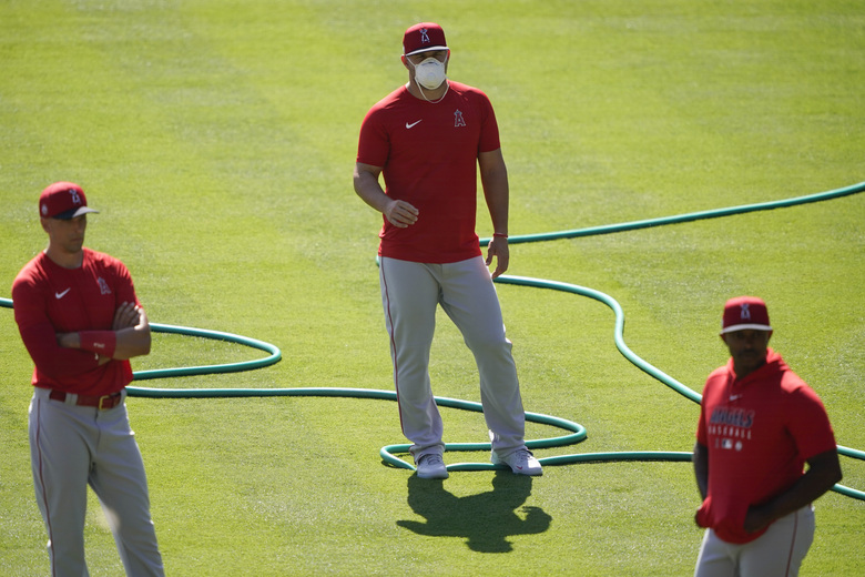 Los Angeles Angels center fielder Mike Trout (27) stands on the field wearing a face mask during a baseball practice at Angels Stadium on Friday, July 3, 2020, in Anaheim, Calif. (AP Photo/Ashley Landis)