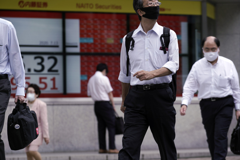 People wearing a face mask to help curb the spread of the coronavirus near an electronic stock board showing Japan's Nikkei 225 index at a securities firm in Tokyo Monday, July 13, 2020. Asian shares rose Monday, cheered by recent upbeat projections on a global rebound tempered with worries about disappointment that could follow. (AP Photo/Eugene Hoshiko)