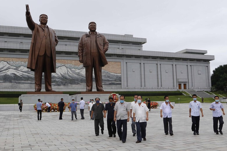 """People visit the statues of former North Korean leaders Kim Il Sung, left, and Kim Jong Il, right, to lay flowers on the occasion of the 67th anniversary of the end of the Korean War, which the country celebrates as the day of """"victory in the fatherland liberation war"""" in Pyongyang, Monday, July 27, 2020. (AP Photo/Jon Chol Jin)"""