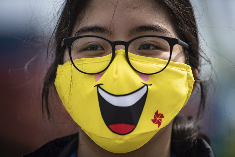 Ride operator Van Mai wears a face mask while working at the Playland amusement park at the Pacific National Exhibition, in Vancouver, British Columbia, on July 10, 2020. (Darryl Dyck/The Canadian Press via AP)