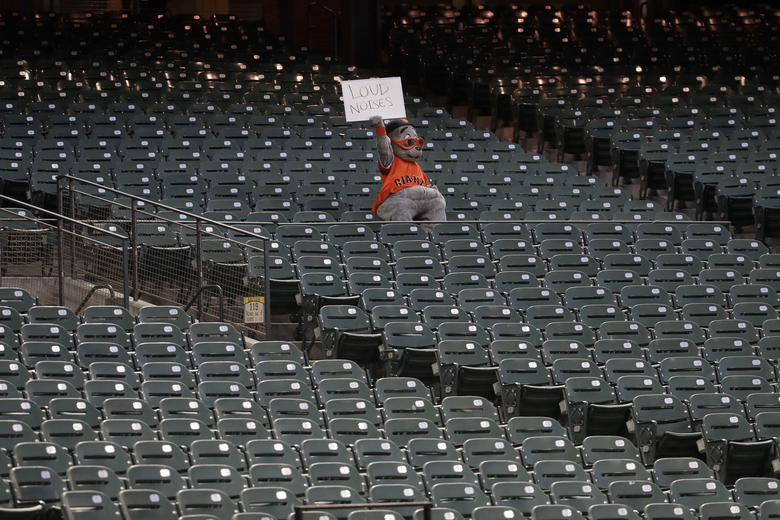 San Francisco Giants mascot Lou Seal holds up a sign during the fifth inning of an exhibition baseball game between the Giants and the Oakland Athletics in San Francisco, Tuesday, July 21, 2020. (AP Photo/Jeff Chiu)