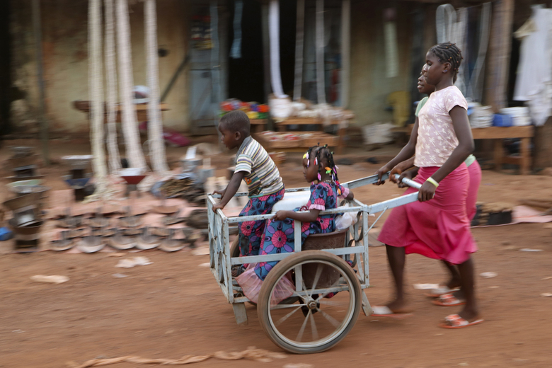 Girls push children in a cart near the market in the town of Hounde, Tuy Province, in southwestern Burkina Faso on Thursday, June 11, 2020. (AP Photo/Sam Mednick)