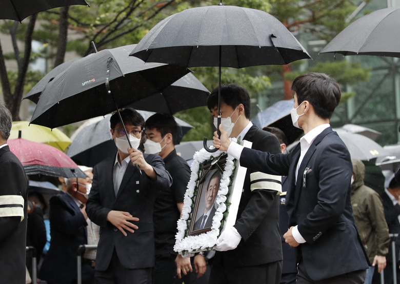 A man carries a portrait of late Seoul Mayor Park Won-soon after his official funeral outside the Seoul City Hall in Seoul, South Korea, Monday, July 13, 2020. Masked mourners gave speeches and laid flowers before the coffin of Seoul's mayor during his funeral Monday, while a live broadcast online drew a mixture of condolence messages and insults.(AP Photo/Lee Jin-man)