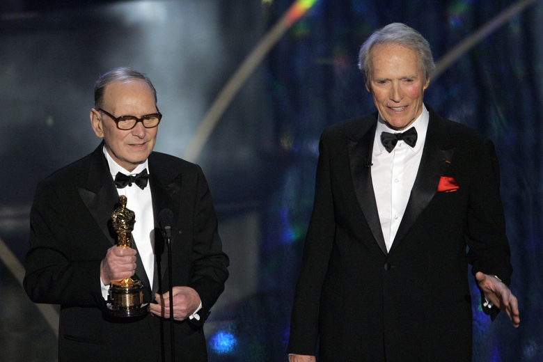"""FILE – In this Feb. 25, 2007 file photo, Italian composer Ennio Morricone, left, accepts an honorary Oscar for his contributions to the art of film music as director Clint Eastwood looks on during the 79th Academy Awards telecast in Los Angeles. Morricone, who created the coyote-howl theme for the iconic Spaghetti Western """"The Good, the Bad and the Ugly"""" and the soundtracks such classic Hollywood gangster movies as """"The Untouchables,"""" died Monday, July 6, 2020 in a Rome hospital at the age of 91. (AP Photo/Mark J. Terrill, file)"""