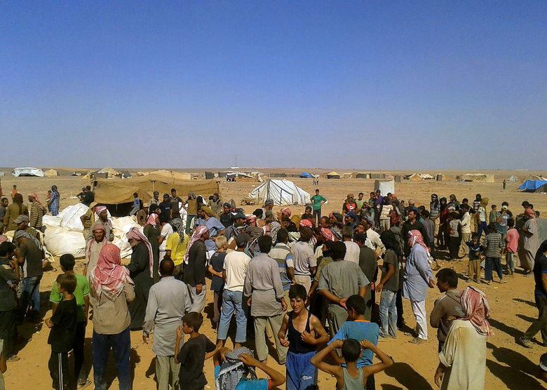 FILE – In this Aug. 4, 2016 file photo, people gather to take basic food stuffs and other aid from community leaders charged with distributing equitably the supplies to the 64,000-person refugee camp called Ruqban on the Jordan-Syria border. Over the last two days, members of the UN Security Council have been haggling over cross-border aid delivery to Syria, with Russia, a major ally of the Syria government, working to reduce the delivery of U.N. humanitarian aid to Syria's last rebel-held northwest down from two crossings to just one. A final vote is expected Friday, July 10, 2020 as western countries push on a new resolution to keep the two crossings open for six months, instead of a year. (AP Photo, File)