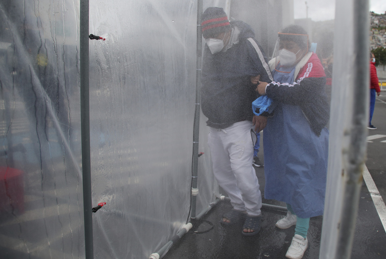 A man experiencing difficulty in breathing is accompanied by a relative as they enter a decontamination chamber at the Seguro Social Hospital in Quito, Ecuador, Wednesday, July 29, 2020. The Ecuadorian capital has experienced a surge in COVID-19 cases since the government started to reopen the economy last month. (AP Photo/Dolores Ochoa)