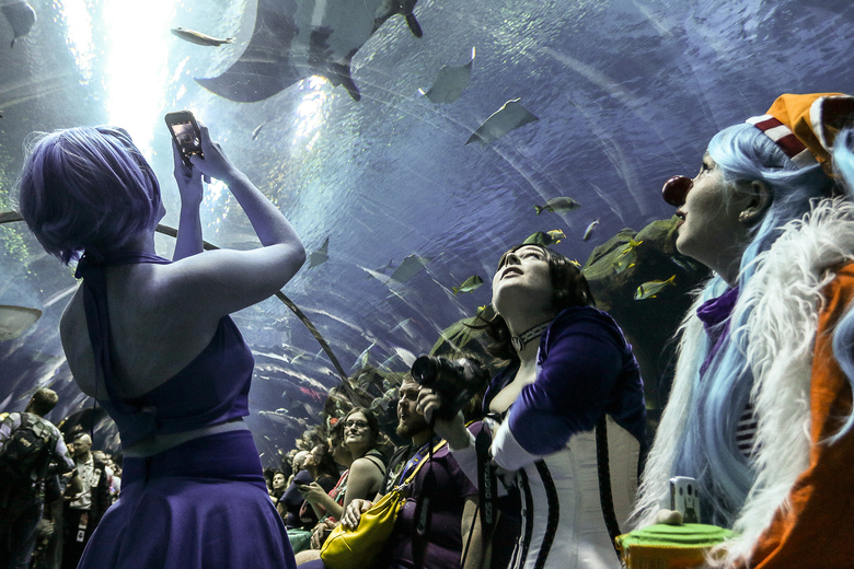 FILE – In this Saturday, Sept. 5, 2015, photo, three women in costumes look at sea life swimming above them during a private party held at the Georgia Aquarium as part of Dragon Con in Atlanta. Officials announced Monday, July 6, 2020 that Dragon Con will be canceled for 2020 in response to the coronavirus pandemic. Dragon Con was originally set to take place over Labor Day weekend. It will instead be moved online for a virtual event. (AP Photo/Ron Harris, File)