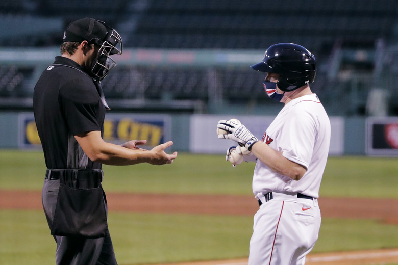 Boston Red Sox batboy Chris Cundiff, right, brings fresh baseballs to home plate umpire Adam Beck during an exhibition baseball game agains the Toronto Blue Jays, Tuesday, July 21, 2020, at Fenway Park in Boston. (AP Photo/Charles Krupa)