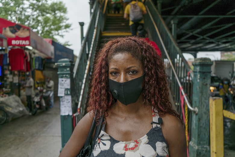 """Damiana Reyes, 44. a Dominican hairstylist whose father died of coronavirus in April, poses for a portrait in the Corona neighborhood of the Queens borough of New York on July 24, 2020. """"All my clients ask about him and then, when I return home, people ask me in the street where he is. It's a constant reminder that he is not around anymore,"""" said Reyes, who thinks her father got sick while playing dominoes at a day care center for elders. The Latino neighborhood was among the hardest hit places in the world. (AP Photo/Marshall Ritzel)"""