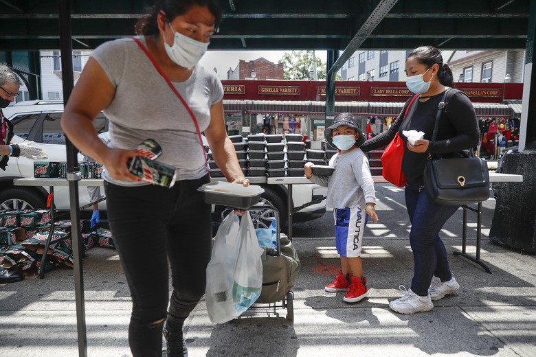 Pedestrians wearing protective masks collect food donations during the COVID-19 pandemic, Tuesday, June 23, 2020, in the Corona neighborhood of the Queens borough of New York. (AP Photo/John Minchillo)