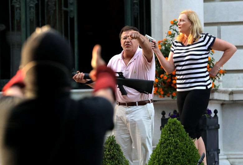 FILE – In this June 28, 2020 file photo, armed homeowners Mark and Patricia McCloskey, standing in front their house along Portland Place confront protesters marching to St. Louis Mayor Lyda Krewson's house in the Central West End of St. Louis. St. Louis' top prosecutor told The Associated Press on Monday, July 20, 2020 that she is charging a white husband and wife with felony unlawful use of a weapon for displaying guns during a racial injustice protest outside their mansion. (Laurie Skrivan/St. Louis Post-Dispatch via AP File)