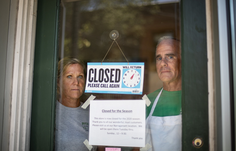 """Steve, right, and Chris Brophy, husband and wife owners of Brickley's Ice Cream, look out from the store they closed after teenage workers were harassed by customers who refused to wear a mask or socially distance, in Wakefield, R.I., Wednesday, July 29, 2020. """"Some of them don't believe it's real (COVID-19) and some don't think it's a big deal, I do,"""" Steve Brophy said, adding that he would rather close than put young workers and customers at risk of harassment, and the virus. """"It's like it's OK to be a jerk in this environment."""" (AP Photo/David Goldman)"""