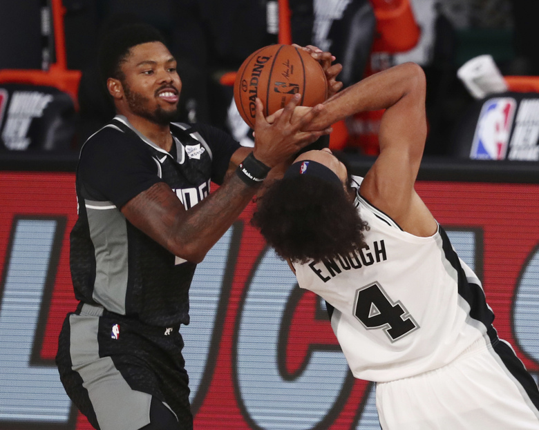 Sacramento Kings guard Kent Bazemore (26) battle for a loose ball San Antonio Spurs guard Derrick White (4) during the second half of an NBA basketball game Friday, July 31, 2020, in Lake Buena Vista, Fla. (Kim Klement/Pool Photo via AP)